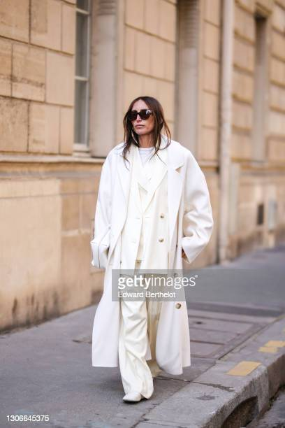 Chloe Harrouche @louloudesaison wears sunglasses, a full Loulou Studio look made of a white oversize wool long coat, a white t-shirt, a cream-color...