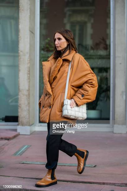 Chloe Harrouche seen wearing brown jacket, black pants, brown boots, white Bottega Veneta bag outside Lanvin during Paris Fashion Week - Menswear F/W...
