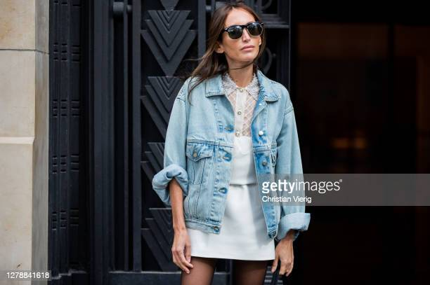 Chloe Harrouche seen wearing denim jacket, white dress, sheer tights, Prada bag outside Miu Miu lunch during Paris Fashion Week - Womenswear Spring...