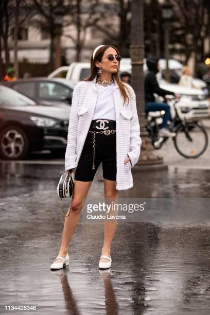 Chloe Harrouche, wearing a white t-shirt, black biker shorts, Chanel belt, white heels, white jacket, black and white bag and white hairband, is seen...