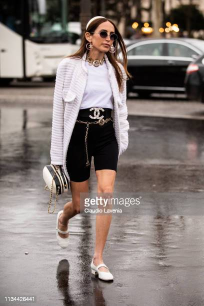Chloe Harrouche wearing a white tshirt black biker shorts Chanel belt white heels white jacket black and white bag and white hairband is seen outside...