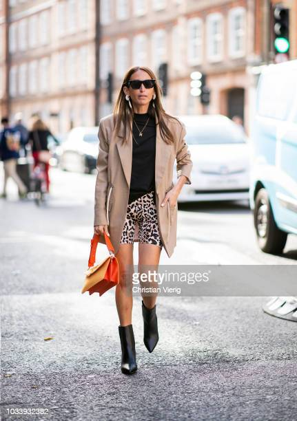Chloe Harrouche wearing cycle pants with leopard print beige blazer orange JW Anderson bag boots is seen outside JW Anderson during London Fashion...