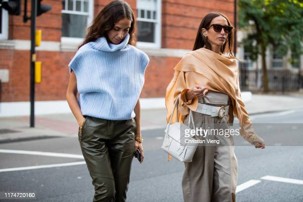 Chloe Harrouche wearing high waist grey pants, orange pastel wrapped top white bag and Erika Boldrin wearing turqouis slipover, olive pants seen...