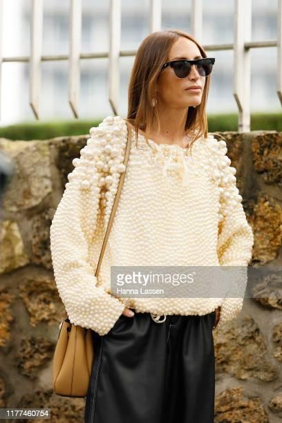 Chloe Harrouche wearing Loewe ivory top with pearl detail and black leather pants outside Loewe during Paris Fashion Week - Womenswear Spring Summer...