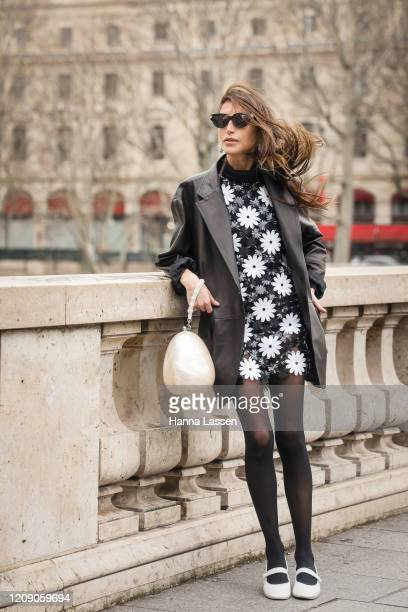 Chloe Harrouche wearing Paco Rabbane black leather jacket, daisy dress and white clutch outside the Paco Rabanne show during the Paris Fashion Week...