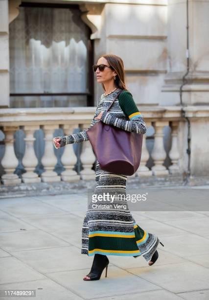 Chloe Harrouche wearing striped dress, bordeaux bag seen outside Victoria Beckham during London Fashion Week September 2019 on September 15, 2019 in...