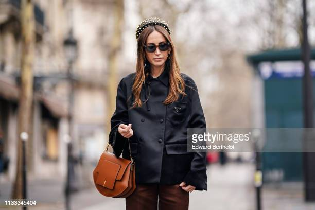 Chloe Harrouche wears a headband a black jacket a brown leather bag shorts black shoes earrings sunglasses outside Altuzarra during Paris Fashion...