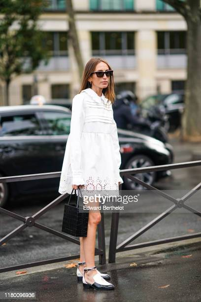 Chloe Harrouche wears earrings, Chanel sunglasses, a gathered white mini dress with a frilly collar and a white lace hem, a black crocodile pattern...