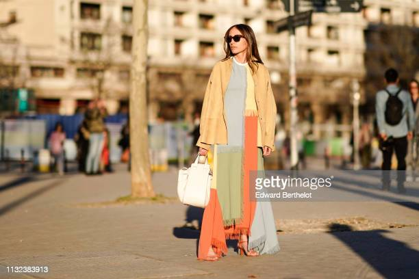 Chloe Harrouche wears sunglasses a beige jacket a multicolor fringed patchwork dress a white bag outside Koche during Paris Fashion Week Womenswear...