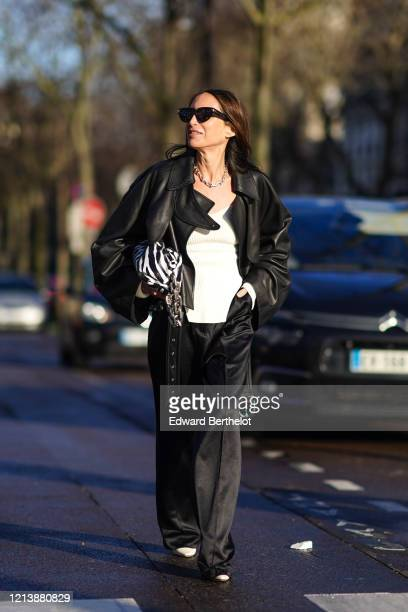 Chloe Harrouche wears sunglasses, a black leather oversized jacket, a black and white zebra print bag, a white top, black flared pants, pointy shoes,...