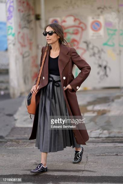 Chloe Harrouche wears sunglasses, a brown long jacket, a black top, a gray pleated skirt, a leather brown and black Loewe bag, black and white shoes,...