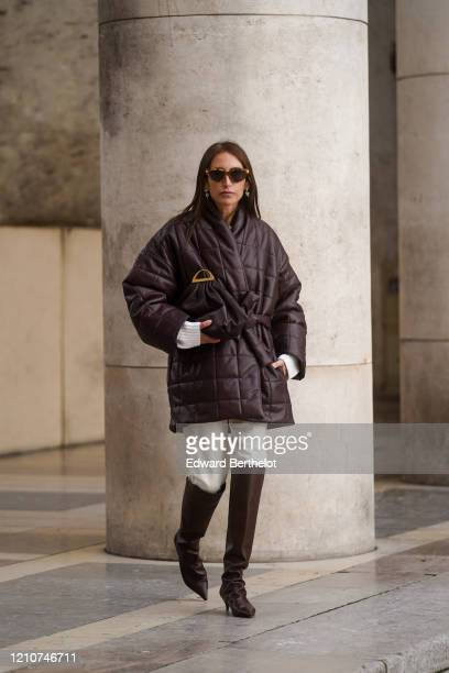 Chloe Harrouche wears sunglasses a brown quilted oversized coat a puff bag white pants brown leather pointy boots outside Gauchere during Paris...
