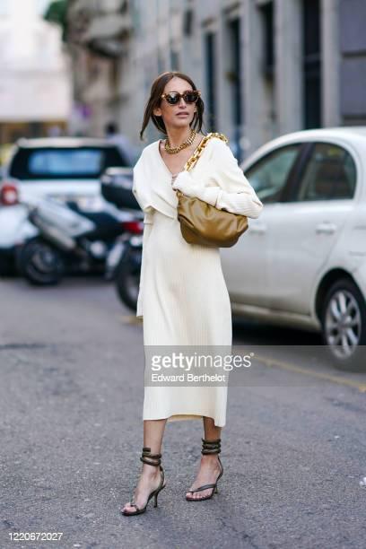 Chloe Harrouche wears sunglasses, a golden necklace, a khaki leather Bottega Veneta bag, a white dress, shoes, outside Max Mara, during Milan Fashion...