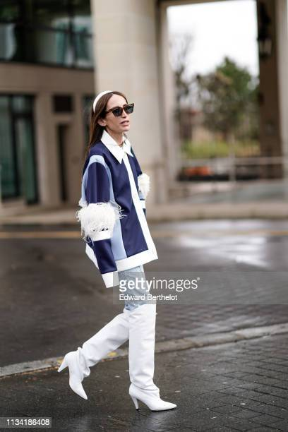 Chloe Harrouche wears sunglasses a white headband a blue and white jacket with white faux fur on the sleeve denim pants white boots outside Miu Miu...