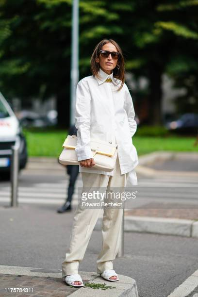 Chloe Harrouche wears sunglasses a white shirt a white bag pants quilted sandals outside the Fendi show during Milan Fashion Week Spring/Summer 2020...