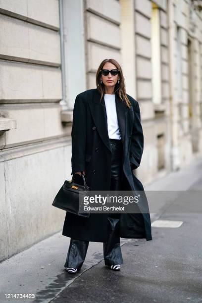 Chloe Harrouche wears sunglasses, an oversized long coat, a white t-shirt, black leather flared pants, black and white zebra print pointy shoes, a...