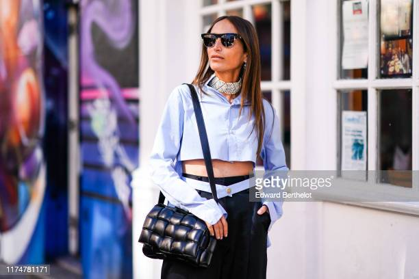 Chloe Harrouche wears sunglasses earrings a beaded choker a pale blue cropped shirt black pants a quilted bag during London Fashion Week September...