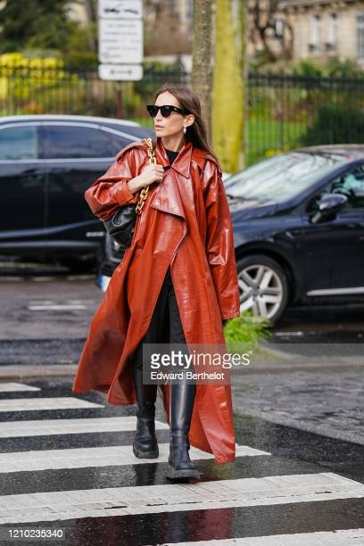 Chloe Harrouche wears sunglasses earrings a Bottega Veneta bag with a golden chain handle a red leather trench long coat black pants black boots...