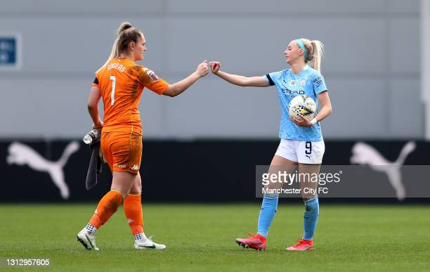 Chloe Kelly of Manchester City is congratulated on her three goals by Sian Rogers of Aston Villa as she leaves the pitch with the match ball during...