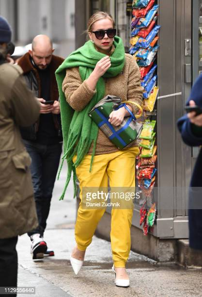 Chloe King is seen wearing a green scarf, brown sweater, yellow leather pants, white heels and Michael Kors bag outside the Michael Kors show during...
