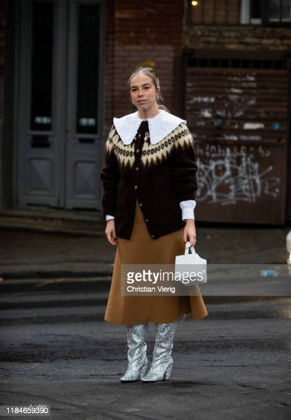 Chloe King seen wearing brown button up jacket white blouse with collar brown midi skirt white bag silver boots during day 1 of the MercedesBenz...