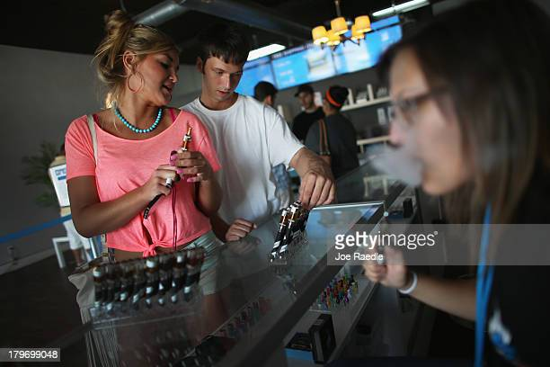 Chloe Lamb and Jacob Knight shop for an E liquid flavor for her electronic cigarette at the Vapor Shark store on September 6 2013 in Miami Florida...
