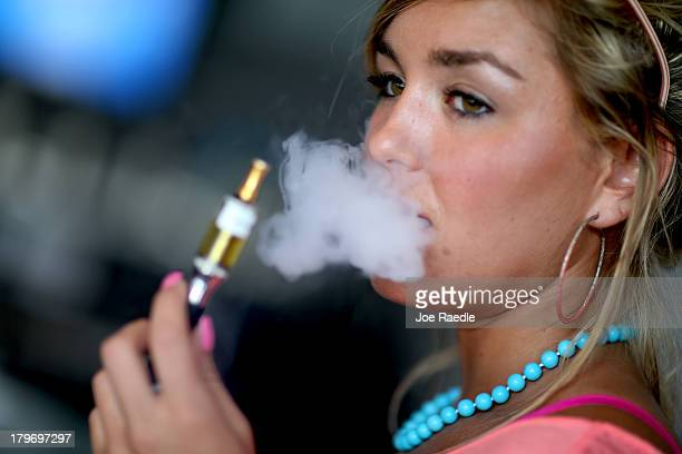 Chloe Lamb enjoys an electronic cigarette at the Vapor Shark store on September 6 2013 in Miami Florida Ecigarette manufacturers have seen a surge in...
