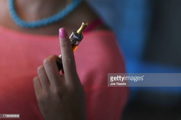 Chloe Lamb tries a flavor of E liquid in her electronic cigarette as she shops for a flavor at the Vapor Shark store on September 6 2013 in Miami...