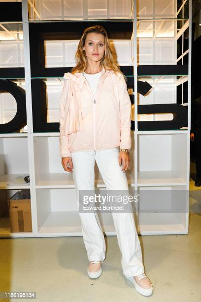 Chloe Lecareux wears a pale pink jacket, a white t-shirt, white pants, sneakers shoes, during Moncler House Of Genius : Paris Opening Event at...