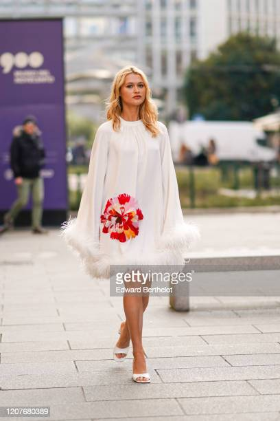 Chloe Lecareux wears a white dress with embroidered red/pink flower and fluffy parts, white shoes, outside Vivetta, during Milan Fashion Week...