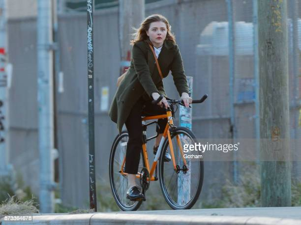 Chloe Moretz bikes under the Williamsburg Bridge on location for 'The Widow' on November 12 2017 in New York City