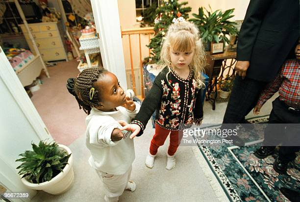 Chloe Ossais, 5 years old, touches Memumatu Mansaray's arm after she removed her prosthetic. Memumatu is being sponsored for the xmas holiday by the...