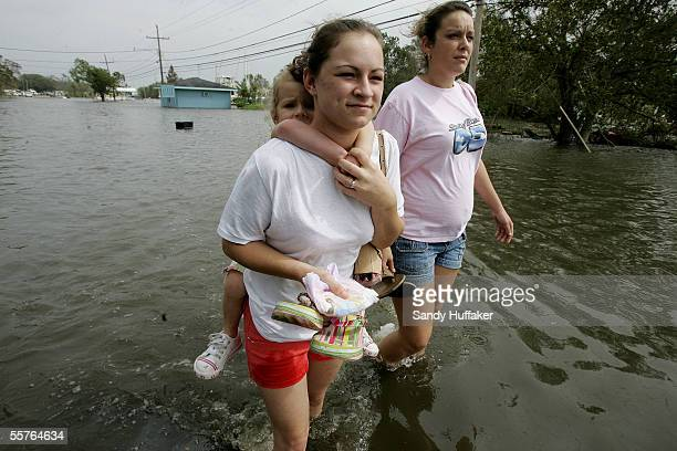 Chloe Rice with her daughter Erica Scott walks to higher ground with friend Nicole Lapeyrouse as flood waters rise due to a levy break September 24...