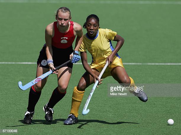 Chloe Rogers of England challenges DeborahAnn Holder of Barbados during the women's field hockey qualifying match at the State Hockey Centre in the...