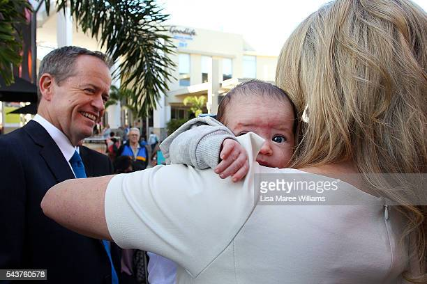 Chloe Shorten holds a baby as Opposition Leader Australian Labor Party Bill Shorten looks on during a visit to the Hyperdome shopping centre on June...