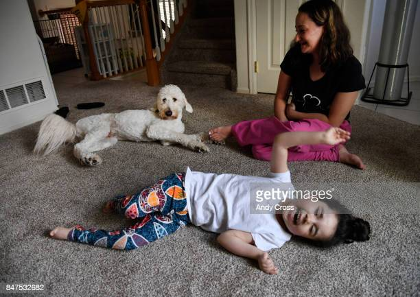 Chloe who has epilepsy wiggles and giggles on the living room floor while her mother Brandis Perry keeps an eye on their service dog Trusty the...