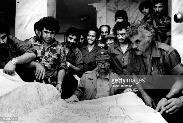 Chmn. Yasser Arafat & mil. Aides pouring over map of Beirut, plotting Palestinian strategy in hideout nr. City during Israeli invasion siege of...