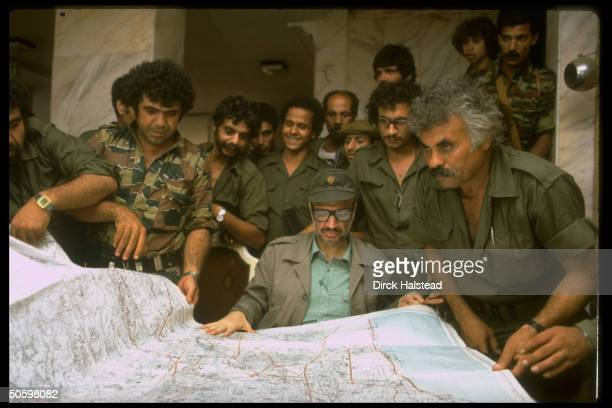 PLO chmn Yasser Arafat mil aides pouring over map of Beirut plotting Palestinian strategy in hideout nr city during Israeli invasion siege of Beirut