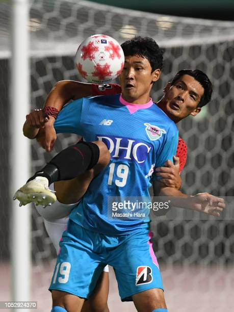Cho Dong Geon of Sagan Tosu and Tomoaki Makino of Urawa Red Diamonds compete for the ball during the 98th Emperor's Cup Quarter Final between Urawa...