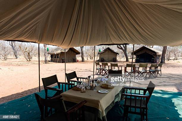 A tented safari camp dining room and canvas chairs in a national park.