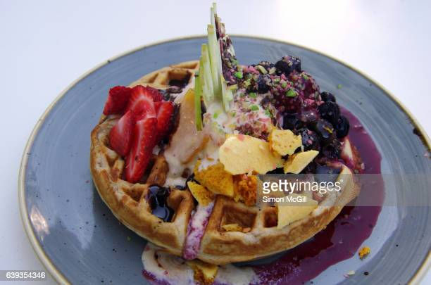 Choc chip waffles with toffee ice cream, chocolate sauce, honeycomb, berry compote, popping candy and fresh strawberries and apple