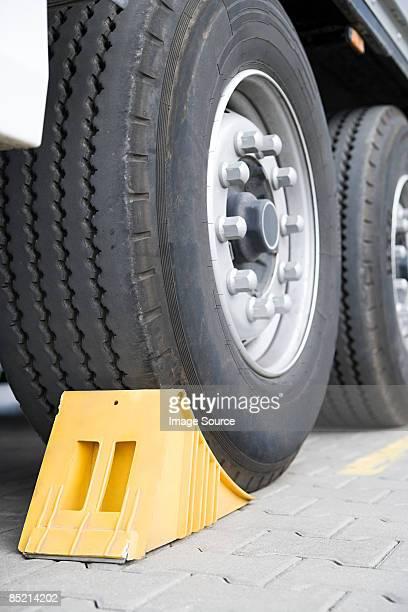 Chock beneath a truck wheel