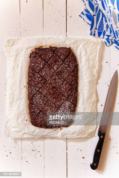 Choco cake brownie served in oven paper and white wood lay. Knife and fantasy blue paper napkin near. No one. Vertical. Overhead.