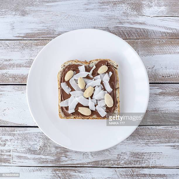 Chocolate, almond and dried coconut on seeds toast.