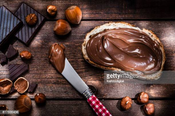 Chocolate and hazelnut spread on bread slice shot on rustic wooden table