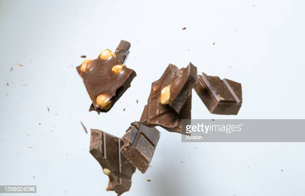 chocolate bar flying in mid air captured with high speed with white background - nougat stock pictures, royalty-free photos & images