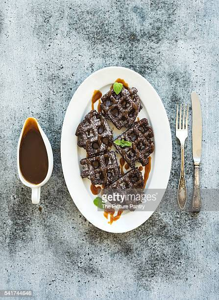 Chocolate Belgian waffles with salted caramel sauce and mint on white ceramic serving plate over gru