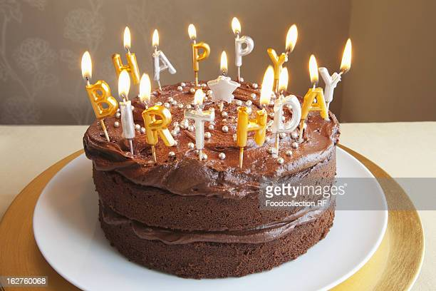chocolate birthday cake with lots of candles - birthday cake lots of candles stock photos and pictures