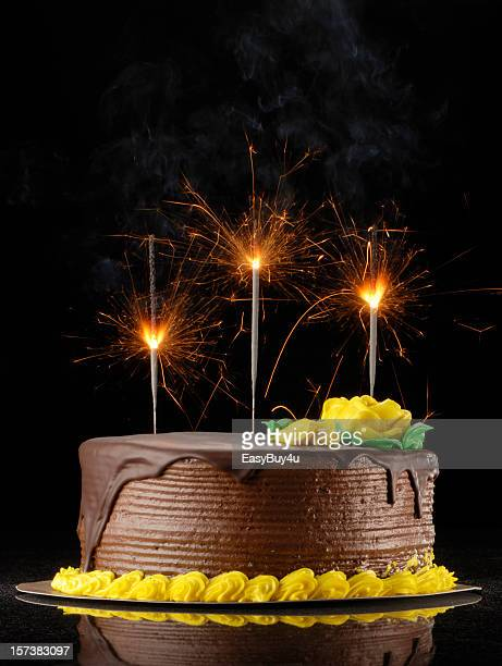 chocolate birthday cake with sparklers on a black background - birthday cake stock photos and pictures