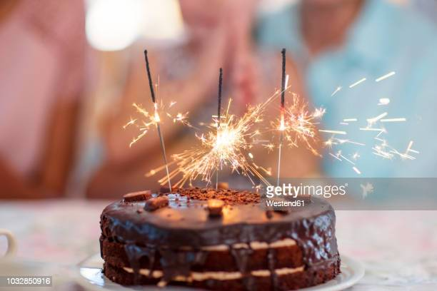 chocolate birthday cake with sprklers - birthday cake stock photos and pictures